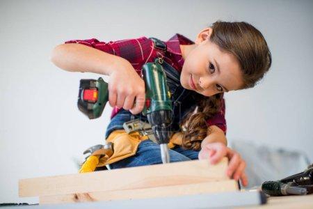 Girl drilling plank