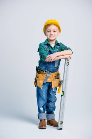 Photo for Cute little boy in yellow hard hat and tool belt holding level tool and smiling at camera - Royalty Free Image