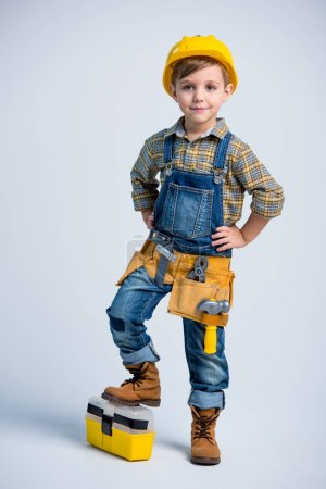 Photo for Cute little boy in yellow hard hat and tool belt smiling at camera on white - Royalty Free Image