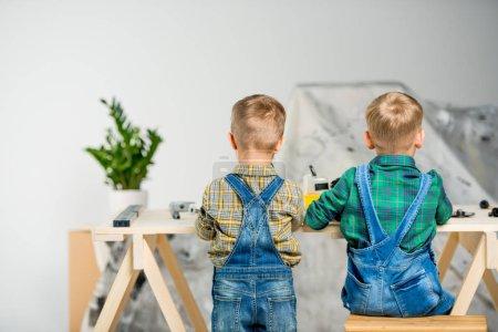 Foto de Vista trasera de dos niños pequeños en overoles de mezclilla jugando en el taller - Imagen libre de derechos