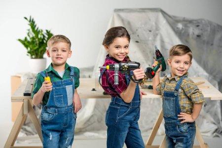 Photo pour Deux petits garçons et fille en atelier outils jouet et souriant à la caméra - image libre de droit