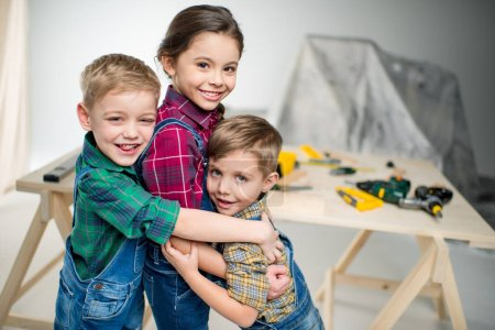 Photo for Two little boys and girl hugging in workshop and smiling at camera - Royalty Free Image