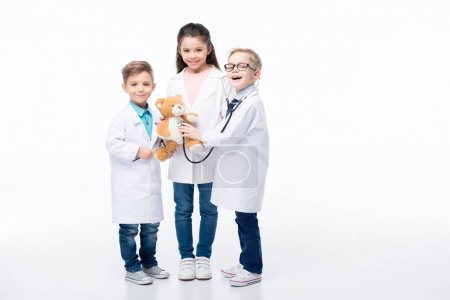 Foto de Adorable smiling kids playing doctors with stethoscope, reflex hammer and teddy bear  isolated on white - Imagen libre de derechos