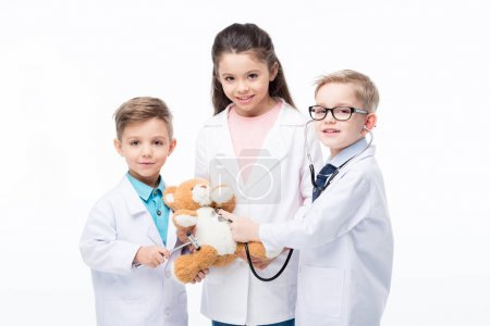 Foto de Cute little kids playing doctors with stethoscope, reflex hammer and teddy bear  isolated on white - Imagen libre de derechos