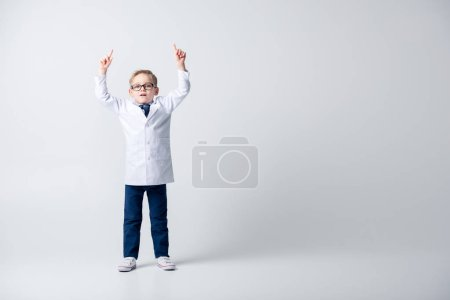 Photo for Shocked little boy in doctor costume and eyeglasses pointing up with fingers isolated on white - Royalty Free Image