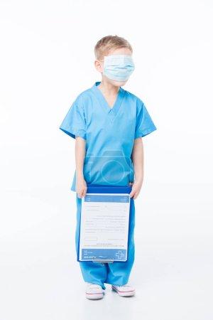 Photo pour Petit garçon dans un masque médical sur le visage tenant presse-papiers tout en jouant médecin isolé sur blanc - image libre de droit