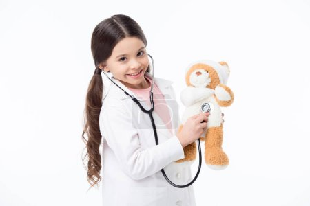 Photo for Smiling little girl playing doctor and listening teddy bear with stethoscope isolated on white - Royalty Free Image