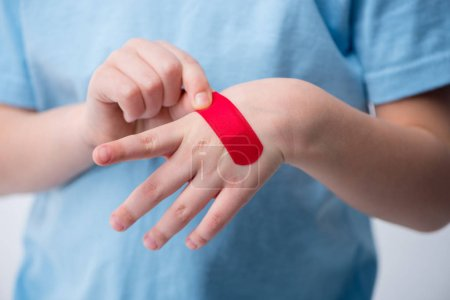 Photo pour Voir section médiane du petit garçon enlevant rouge parch de sa main - image libre de droit