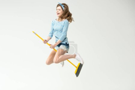 Photo pour Happy beautiful young woman flying on broom isolated on white - image libre de droit