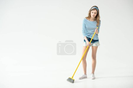 Photo pour Beautiful young woman sweeping with broom isolated on white - image libre de droit