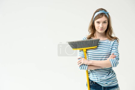 Photo pour Attractive young woman standing with crossed arms and holding broom isolated on white - image libre de droit