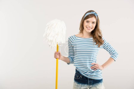 Photo for Attractive young woman with hand on waist holding mop and smiling at camera isolated on white - Royalty Free Image