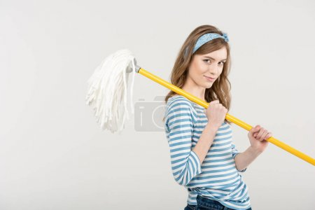 Photo for Attractive young woman holding mop on shoulder and smiling at camera isolated on white - Royalty Free Image