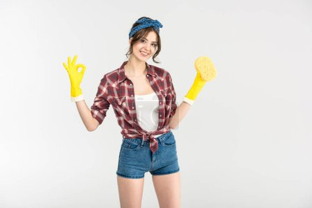 Photo for Attractive young smiling housewife holding sponge and showing ok sign isolated on white - Royalty Free Image