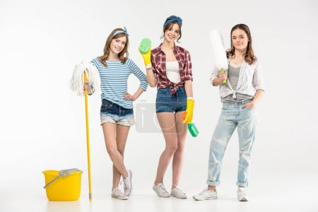 Photo for Attractive young women holding cleaning supplies and smiling at camera  isolated on white - Royalty Free Image