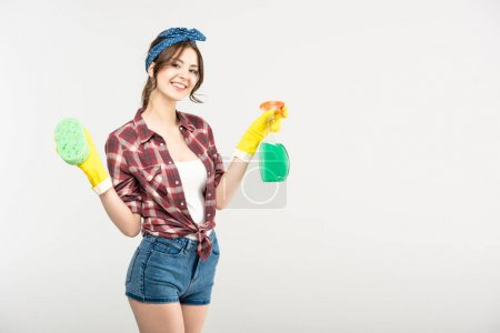 Photo pour Beautiful young woman holding sponge and spray bottle smiling at camera isolated on white - image libre de droit