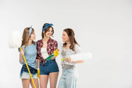 Photo for Three beautiful young women holding cleaning supplies and talking  isolated on white - Royalty Free Image