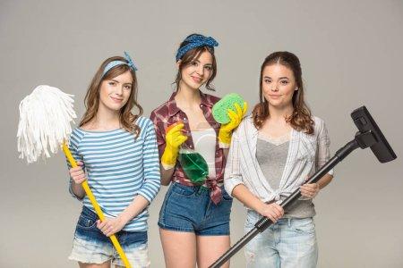 Photo pour Jeunes femmes attirantes tenant des fournitures de nettoyage et souriant à la caméra isolée sur gris - image libre de droit