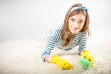 Photo for Young woman in rubber gloves cleaning carpet with sponge and smiling at camera isolated on white - Royalty Free Image