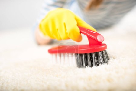 Photo for Close-up partial view of woman in rubber glove cleaning carpet with brush isolated on white - Royalty Free Image