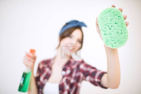 Woman with spray bottle and sponge