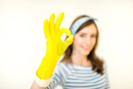 Photo for Young smiling woman in yellow rubber glove showing ok gesture  isolated on white - Royalty Free Image