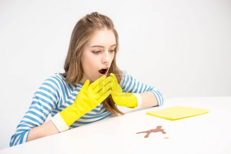 Photo for Shocked young woman in yellow rubber gloves looking at stain  isolated on white - Royalty Free Image