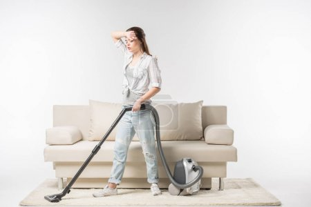 Photo pour Tired young woman cleaning the carpet with vacuum cleaner isolated on white - image libre de droit