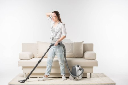 Foto de Tired young woman cleaning the carpet with vacuum cleaner isolated on white - Imagen libre de derechos