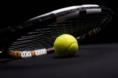 Photo pour Close-up view of tennis ball and racquet isolated on black - image libre de droit