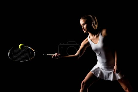 Photo pour Active young woman playing tennis  isolated on black - image libre de droit