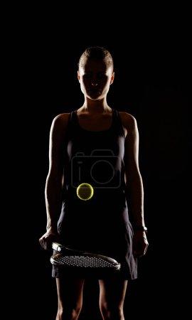 Photo pour Jeune joueuse de tennis concentrée frappant balle avec raquette de tennis isolée sur noir - image libre de droit