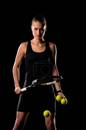 Photo for Young female tennis player holding racket and balls and hitting another one while looking at camera  isolated on black - Royalty Free Image