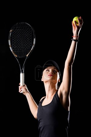 Photo pour Young attractive female tennis player ready to hit the ball with racket isolated on black - image libre de droit