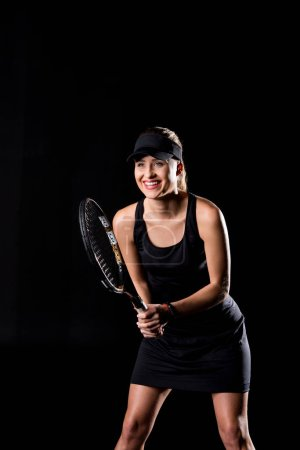 Photo pour Female tennis player holding tennis racket and smiling  isolated on black - image libre de droit