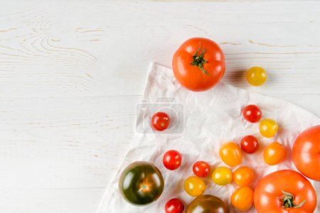 Photo for Top view of various fresh ripe tomatoes on wooden table and white cloth - Royalty Free Image