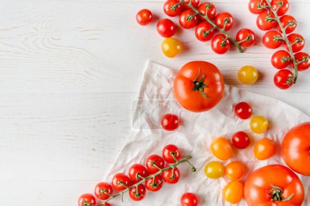 Photo for Top view of fresh ripe tomatoes on wooden table and white cloth - Royalty Free Image