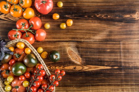 Photo for Top view of fresh ripe tomatoes in basket on wooden table - Royalty Free Image