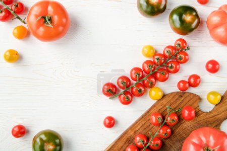 Photo for Top view of various fresh tomatoes on cutting board and wooden table - Royalty Free Image