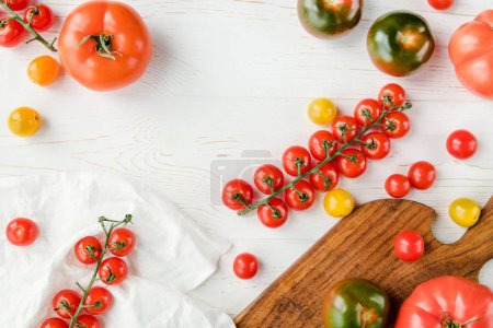 Photo for Top view of various fresh tomatoes on cutting board, white cloth and table - Royalty Free Image