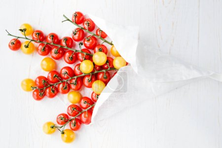 Photo for Top view of fresh ripe red and yellow tomatoes wrapped in white napkin - Royalty Free Image