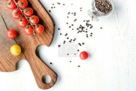 Photo for Top view of fresh tasty tomatoes on cutting board and peppercorns on wooden table - Royalty Free Image