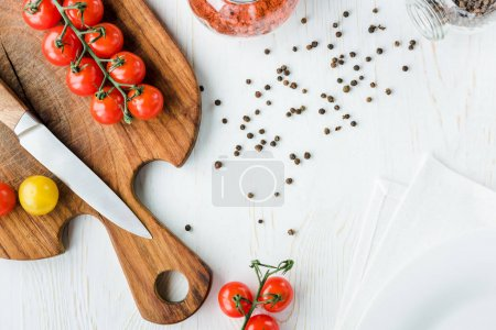 Photo for Top view of fresh ripe tomatoes and knife on cutting board and peppercorns on table - Royalty Free Image