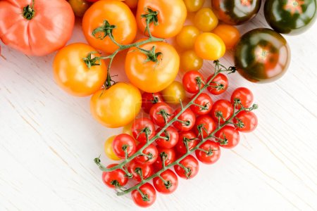 Photo for Close-up top view of various fresh ripe tomatoes on wooden table - Royalty Free Image