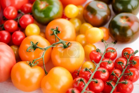 Photo for Close-up view of various fresh ripe tomatoes on wooden table - Royalty Free Image