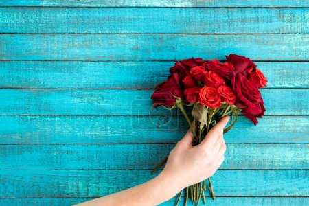 Photo for Top view of hand holding roses bouquet with copy space - Royalty Free Image