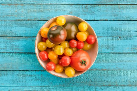 Photo for Top view of tomatoes in bowl on wooden table - Royalty Free Image