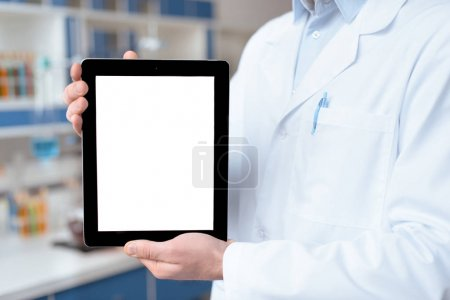 Photo for Close-up partial view of doctor in lab coat showing digital tablet with blank screen - Royalty Free Image