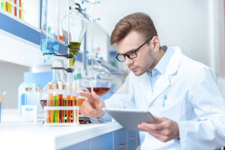 Photo for Young concentrated man scientist holding digital tablet and working with test tubes in lab - Royalty Free Image