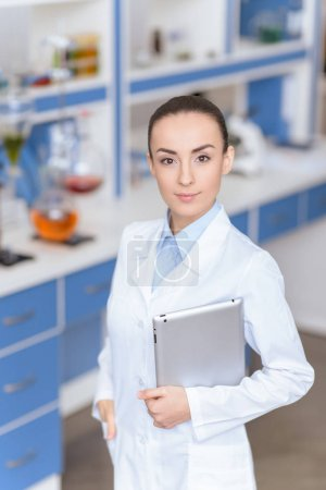 Young confident woman scientist in lab coat holdin...